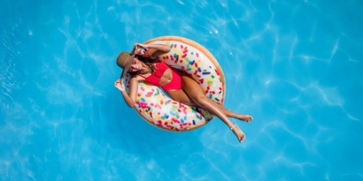 woman in red bikini and sun hat floating in pool on donut floaty