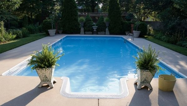 rectangular fiberglass pool with cement patio surrounded by landscaping